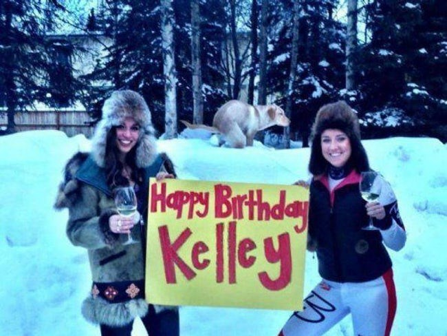 Girls in the snow holding up sign Happy Birthday Kelley with a dog taking a poop in a perfect spot in the pic.