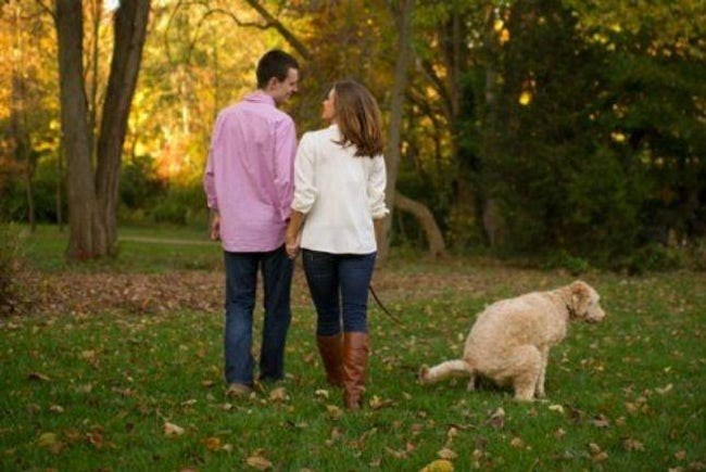 Romantic walk along foliage of color changing trees in the walk ruined by dog taking massive dump next to the couple.