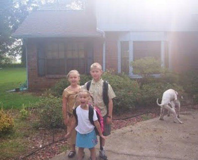Pooping dog in picture of kids on the way to their first day at school.