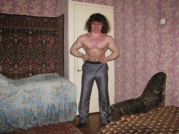 cursed image-Russian man flexing his arms in a bedroom