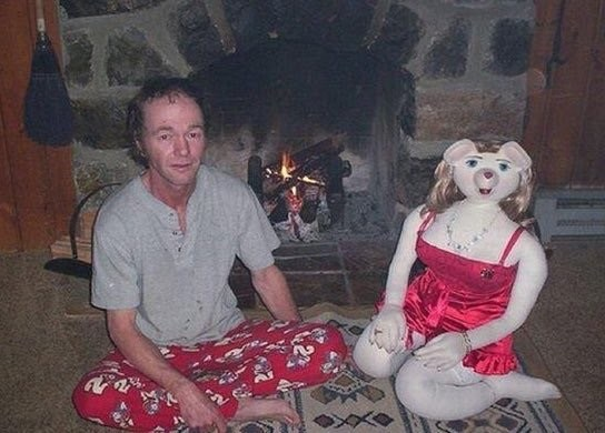 cursed image-man sitting cross legged in front of a fireplace next to a doll