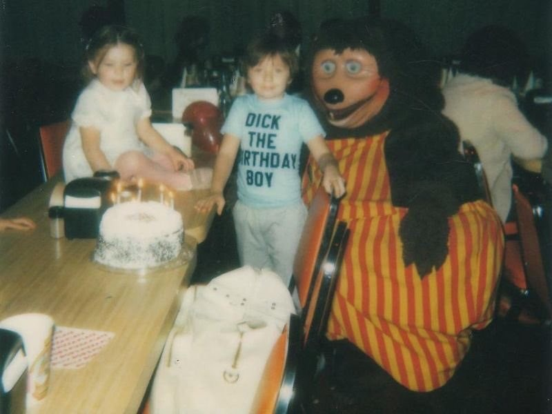 "cursed image-toddler wearing a shirt ""dick the birthday boy"" next to a creepy costume"