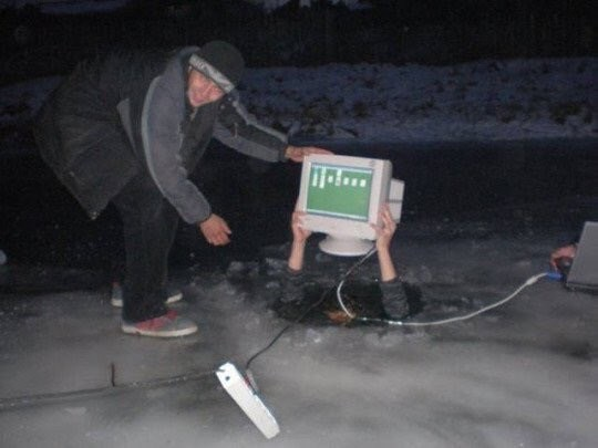 cursed image-man holding a computer while in a hole in the middle of ice