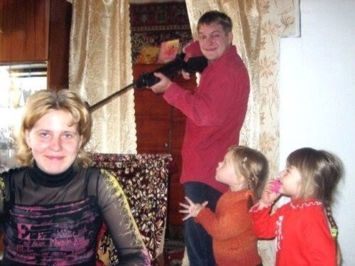 cursed image-man pointing a gun at a woman while 2 girls watch