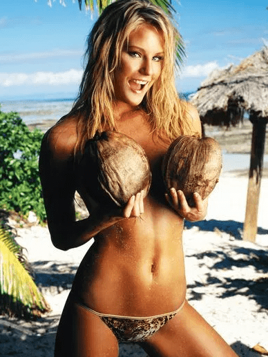 blonde girl in bikini at beach holding coconuts to breasts