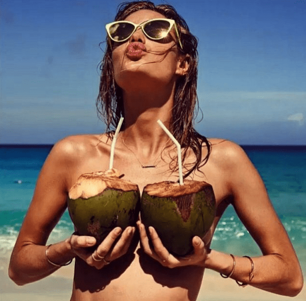 picture of naked woman at beach holding coconuts up to cover breasts