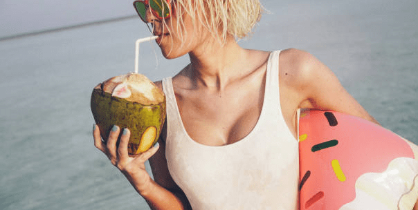 woman in white singlet at beach drinking coconut