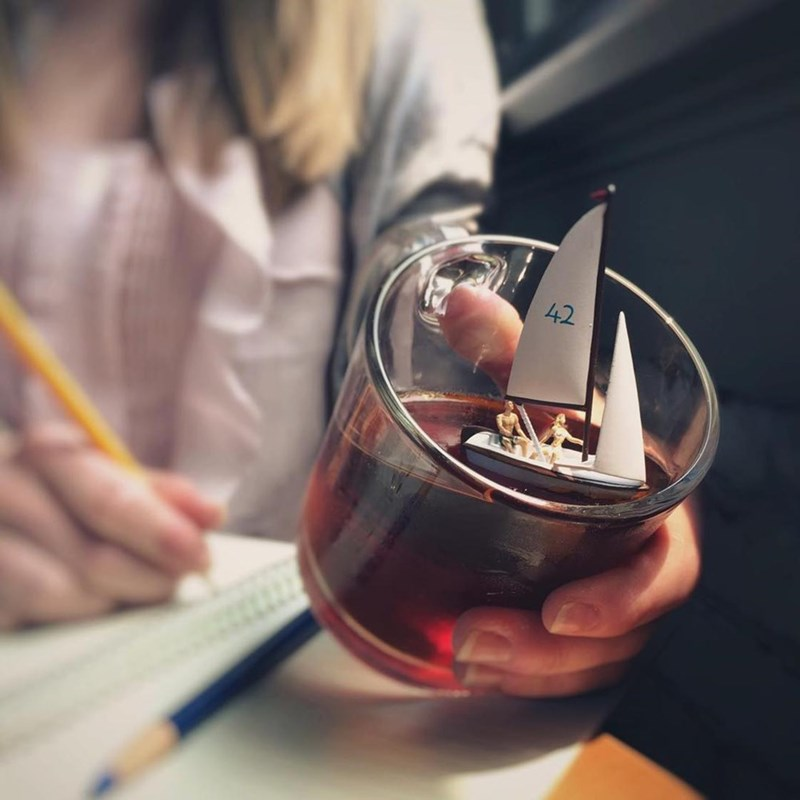 tiny sailboat model in a glass of juice or wine
