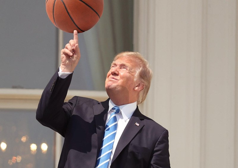 photoshop meme of trump pointing to the solar eclipse with a basketball edited into the picture