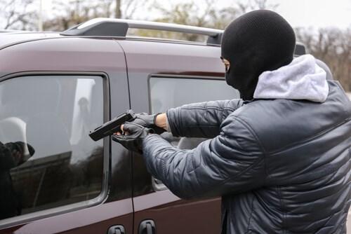 man with balaclava over head holding gun to car window