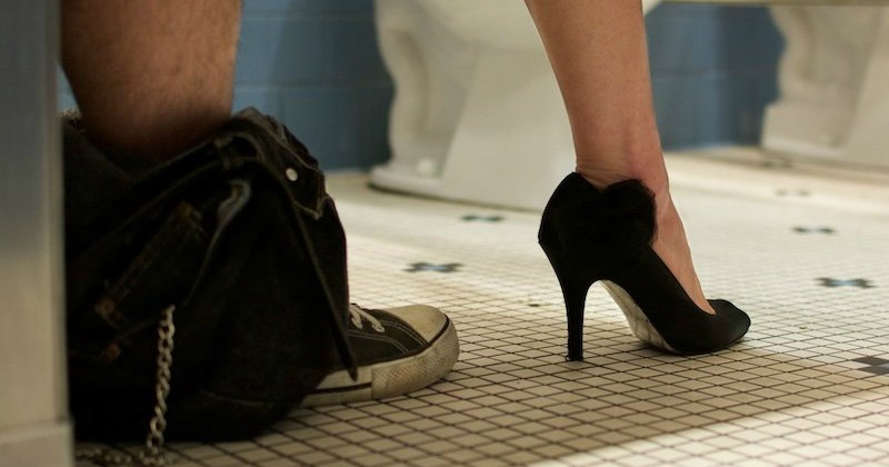 Man and woman in a bathroom stall based on the shoes we see