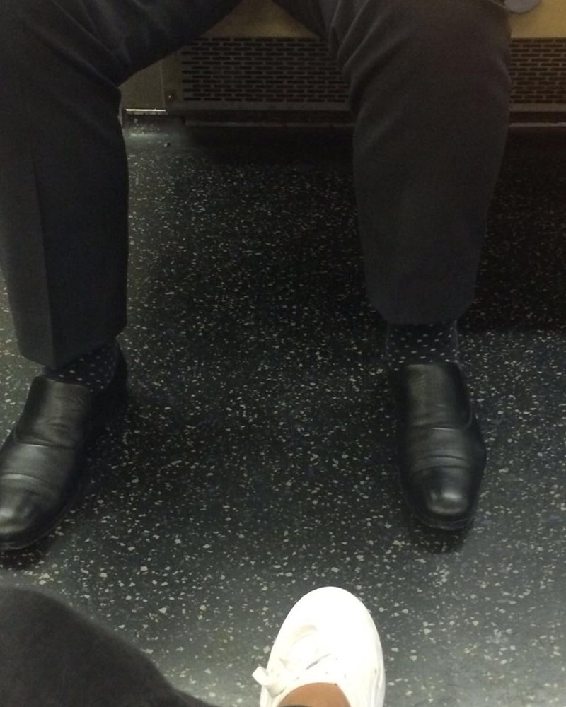 a funny photo of a subway rider wearing socks that match the floor