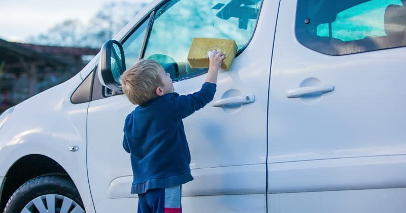 picture little boy washing white van with sponge