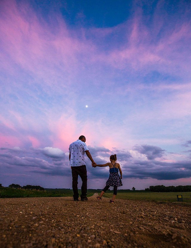 girl walking with dad in an old country road at sunset