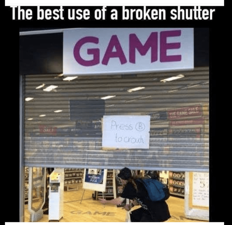 sign on gaming shop telling people to press B to crouch for a broken shutter to enter the store.