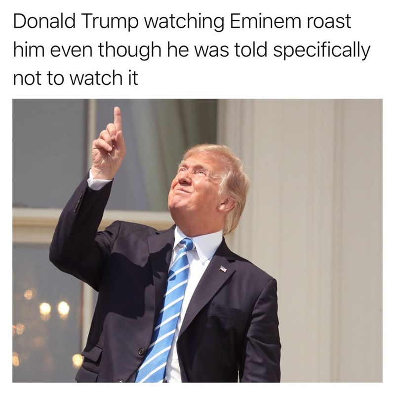 Trump pointing and looking at the solar eclipse captioned as him looking at Eminem roasting him