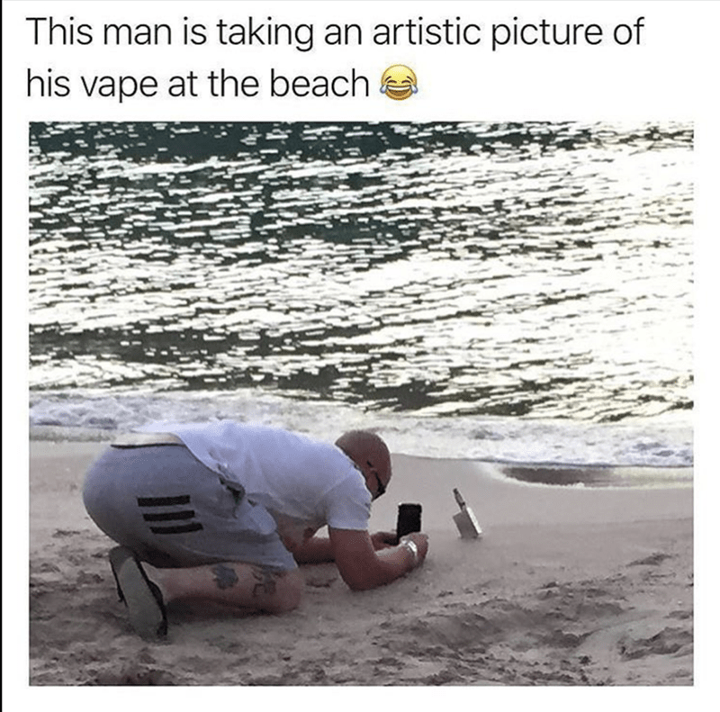 man on the beach taking artistic picture of his vape on the beach