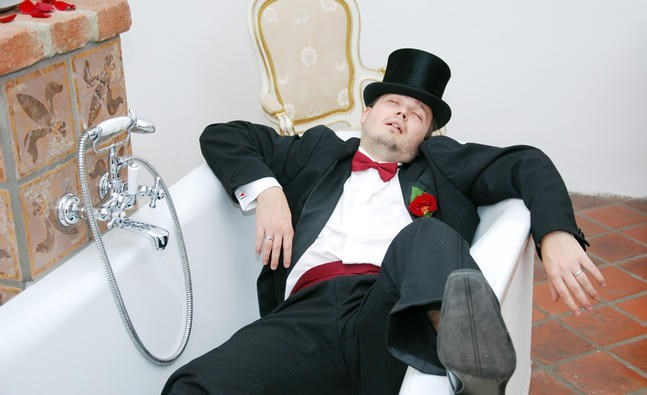 picture drunk groom in bathtub wearing suit and hat