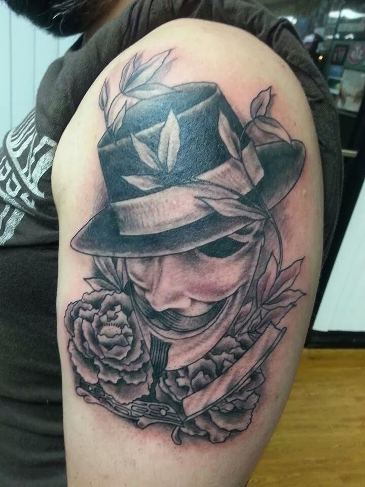 Tattoo of a Guy Fawkes mask wearing a fedora