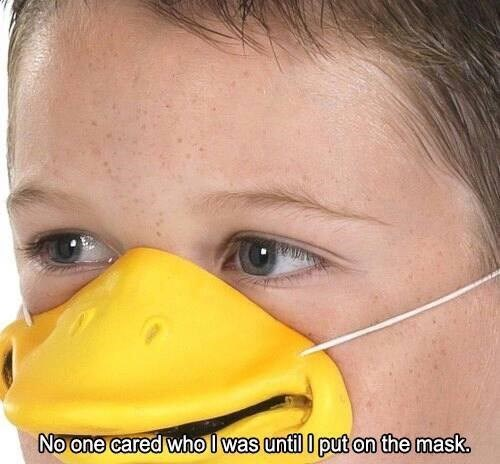 Funny meme of kid wearing silly duck beak mask with cathphrase NO ONE CARED WHO I WAS UNTIL I PUT ON THE MASK