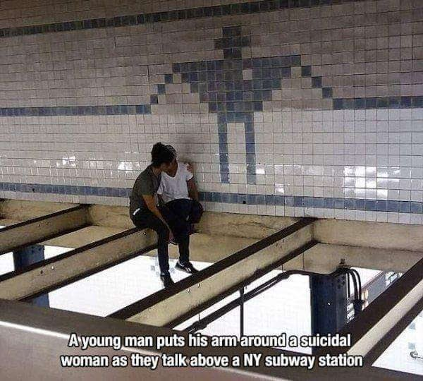 Architecture - Ayoung man puts his armaround asuicidal woman as they talk above a NY subway station