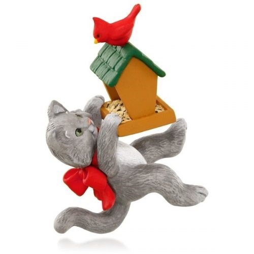 Christmas tree ornament of a cat latching onto a bird house