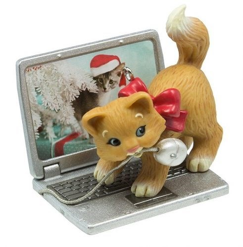 Christmas tree ornament of a cat biting a mouse attached to a computer