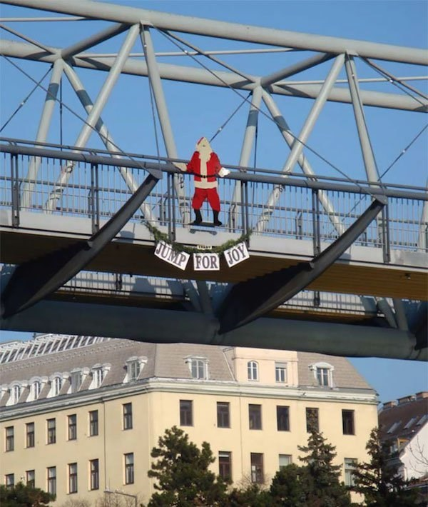 "Christmas design fail of a santa cutout on a bridge that says ""jump for joy"""