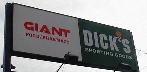 "banner for ""giant"" pharmacy next to banner for ""dick"" store"