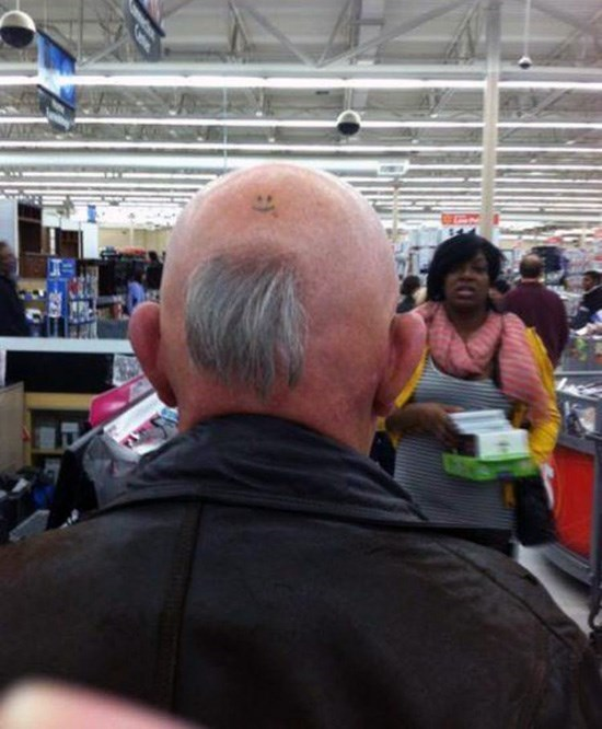bald man with tuft of hair on back of head and smiley face tattoo people of walmart memes