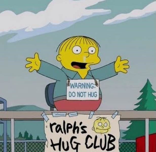 screen grab of Ralph from The Simpsons sitting at a hugging booth wearing a sign warning from hugging him