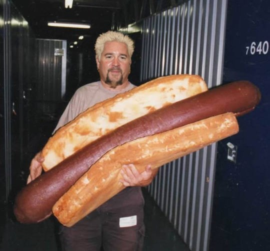 cursed image of Guy Fieri with a massive giant hot dog