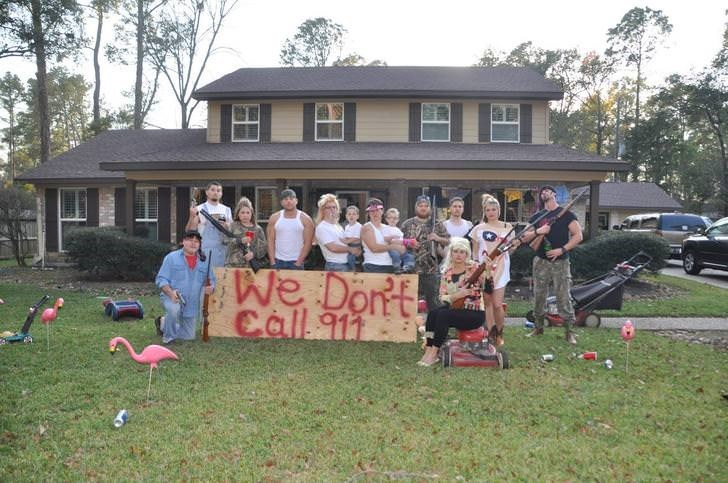 pic of family posing with guns next to a sign that says they don't call 911