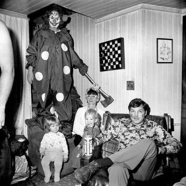 black and white image of family sitting in living room with tall clown holding axe behind them