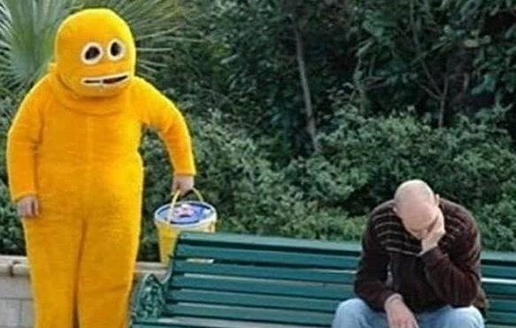 man sitting on bench with chin in hand and person in weird yellow creature suit