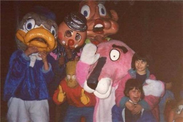 two children standing with characters with creepy costumes on