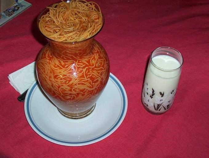 vase full of spaghetti on a plate and glass of milk next to it