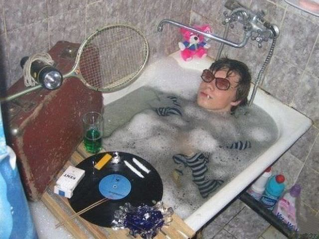 man in bathtub with clothes and sunglasses on and assorted objects around him