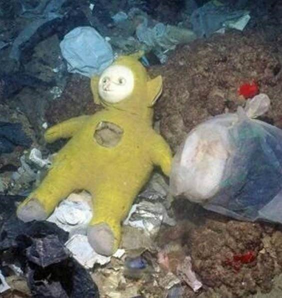 yellow tellytubbies toy lying among garbage