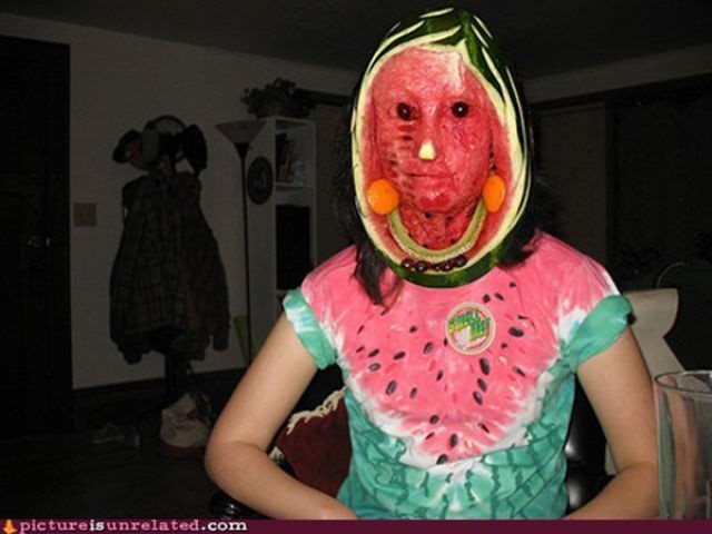 person with watermelon that is carved into a face over their head