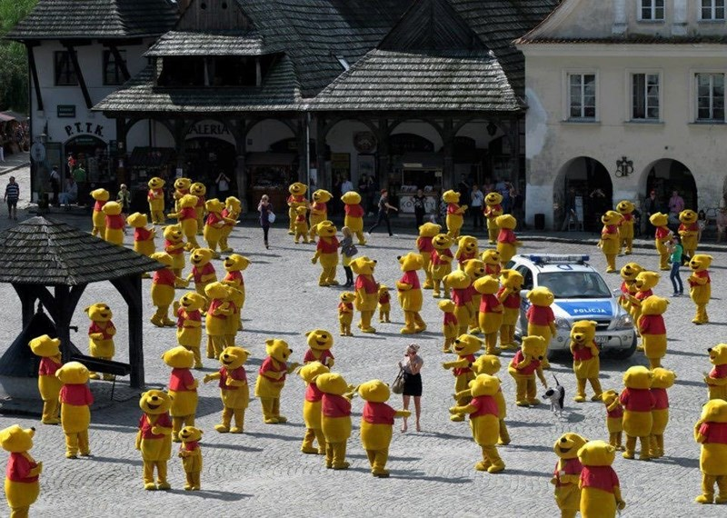 street covered with tens of people dressed in winnie the pooh costumes