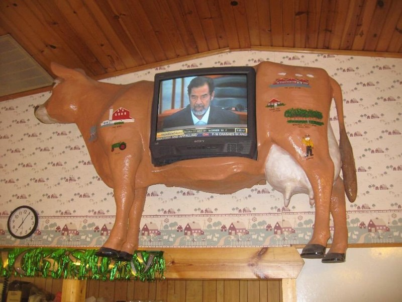 TV on side of fake cow on wall of restaurant