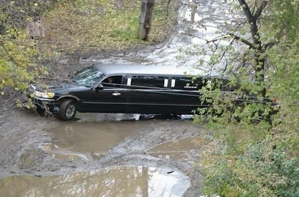 a limousine stuck on a narrow muddy road