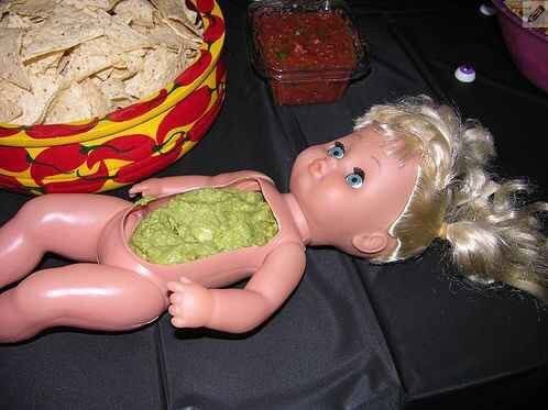 a child's doll with its stomach cut open and green stuff inside there