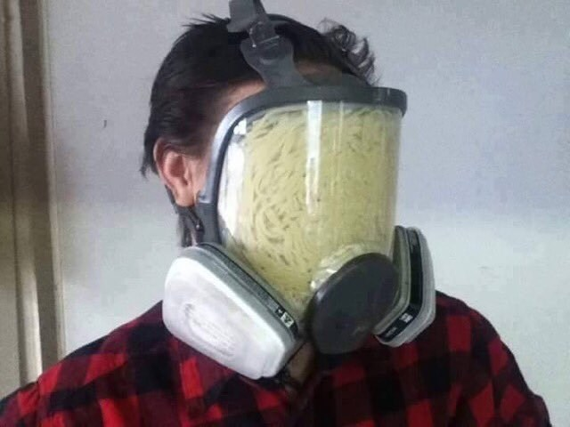 a man wearing a protective gas mask with noodles inside the mask
