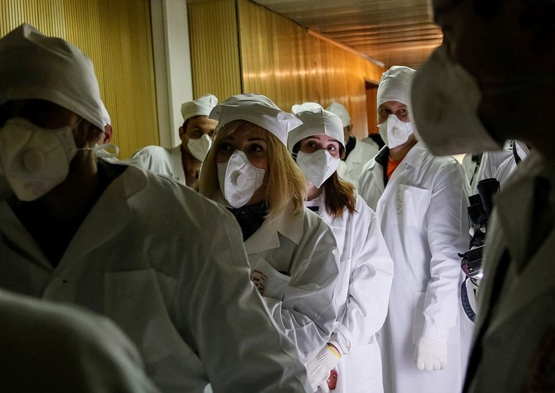 Journalists walk through the corridor of the third reactor at Chernobyl