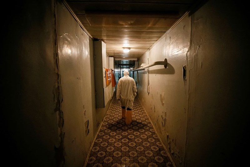 eerie Chernobyl pic of a man walking down a dilapidated hallway wearing a hazmat suit