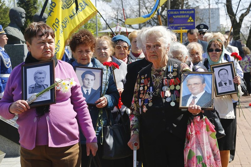 Chernobyl widows hold pictures of their husbands who died in the clean up effort