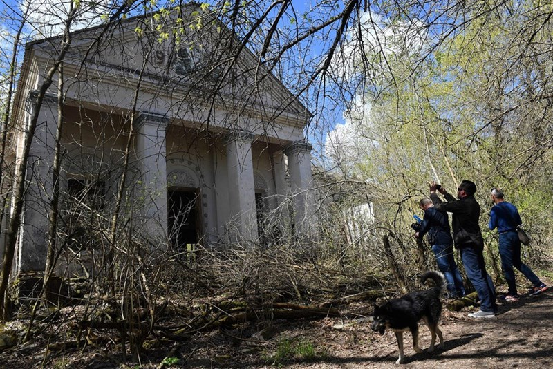 Chernobyl tourists take picture of buildings in Kopachi