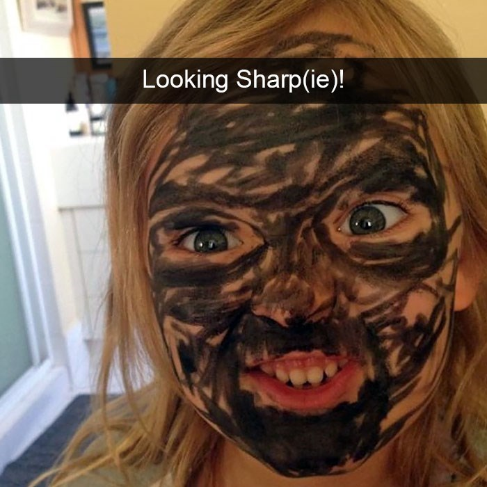 Photo of a small child with black sharpie on her face